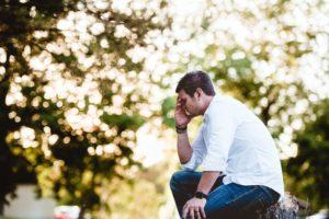 hombre angustiado sentado en un tronco