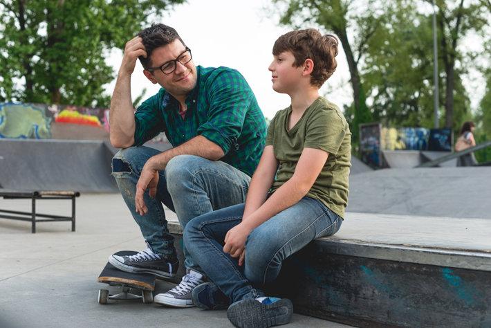 Papa e hijo con una patineta sentados en un parque para patinaje