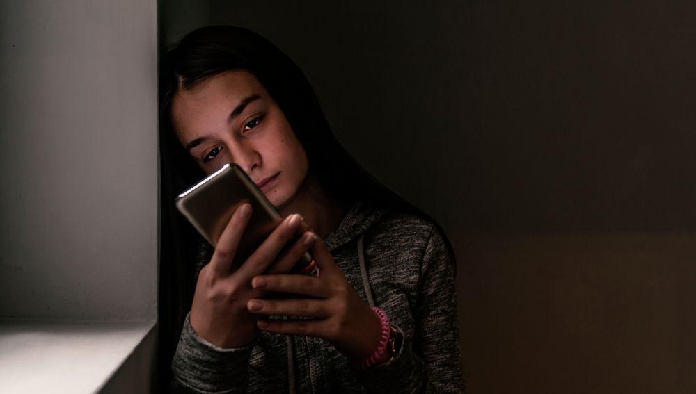 Mujer triste apoyada en la pared viendo su celular
