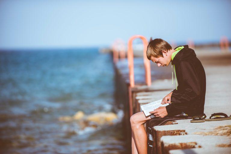 Hombre en un bahía leyendo la bilbia
